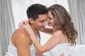 Couple sitting in bed at home — Stock Photo