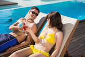 Couple toasting drinks by swimming pool — Stock Photo