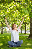 Redhead raising her arms in the park — Stock Photo