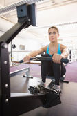 Young woman working on fitness machine at gym — Stock Photo