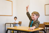 Pupil raising his hand at his desk — Stock Photo