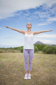 Woman standing with arms raised on countryside landscape — Stock Photo