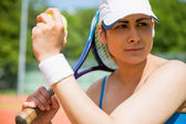 Pretty tennis player sitting on court — Stockfoto