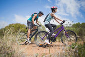 Athletic couple mountain biking — Stock Photo