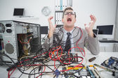 Stressed computer engineer working on broken cables — Stock Photo