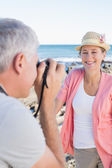 Happy casual man taking a photo of partner by the sea — Stock Photo