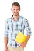 Handsome student holding notepad smiling at camera — Stock Photo