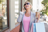 Happy mature woman walking with her shopping purchases — Stock Photo