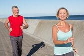 Active senior couple out for a jog — Stock Photo