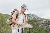 Hiking man holding map on mountain terrain — Stock Photo