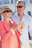 Happy senior couple looking at smartphone holding shopping bags — Stockfoto