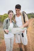 Couple looking at map on mountain terrain — Stock Photo