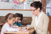 Teacher helping pupil in classroom — Stock Photo