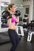 Fit young woman lifting barbell in the gym — Stok fotoğraf