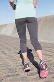 Active senior woman jogging on the pier — Stock Photo