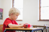 Pupil opening lunchbox at desk in classroom — Stock Photo