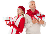 Smiling couple in winter fashion holding presents — Stock Photo