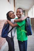 Cute pupils smiling in corridor — Stock Photo