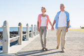 Happy casual couple walking by the coast — Stock Photo