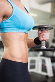 Mid section of fit woman exercising with dumbbell in gym — Stock Photo