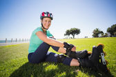 Fit mature woman tying her roller blades on the grass — Stock fotografie