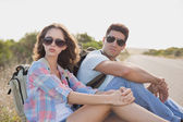 Hiking couple sitting on countryside road — Stock Photo