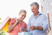 Happy senior couple looking at their purchases — Stock Photo