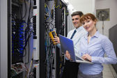 Team of technicians using digital cable — Stock Photo