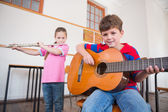 Pupils playing flute and guitar in classroom — Stock Photo