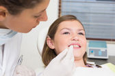 Pediatric dentist examining little girls teeth — Foto Stock