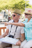Happy tourist couple looking at map in the city — Stok fotoğraf