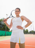 Pretty tennis player holding racket smiling at camera — Stock Photo