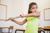 Pupil playing flute in classroom — Stock Photo