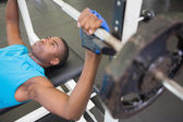 Young man lifting barbell in gym — Foto Stock