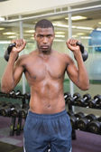 Muscular man lifting kettle bells — 图库照片