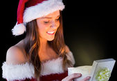 Brunette in santa outfit opening gift — Stock Photo
