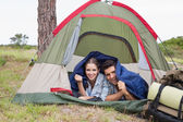 Happy couple lying in tent on countryside landscape — Stock Photo