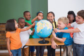 Pupils pointing to globe in classroom — Stock Photo