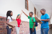 Pupils high fiving in the hallway — Stockfoto