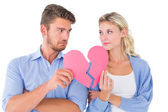 Couple holding two halves of broken heart — Stock Photo
