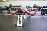 Man exercising with dumbbells in gym — Stock Photo