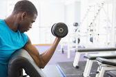 Muscular man exercising with dumbbell — Stock Photo