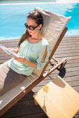 Woman reading book by swimming pool with champagne on table — Stock Photo
