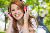 Redhead listening to music in the park — Stockfoto