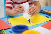 Little boy making art in classroom — Stock Photo