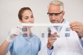 Dentist and assistant studying x-rays — Stock Photo