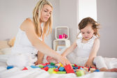 Mother and daughter playing with building blocks on bed — Stock Photo