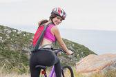 Portrait of athletic woman mountain biking — Stock Photo