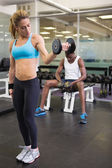 Fit woman exercising with dumbbell in gym — Stok fotoğraf
