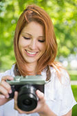 Redhead taking a photo in the park — Stock Photo